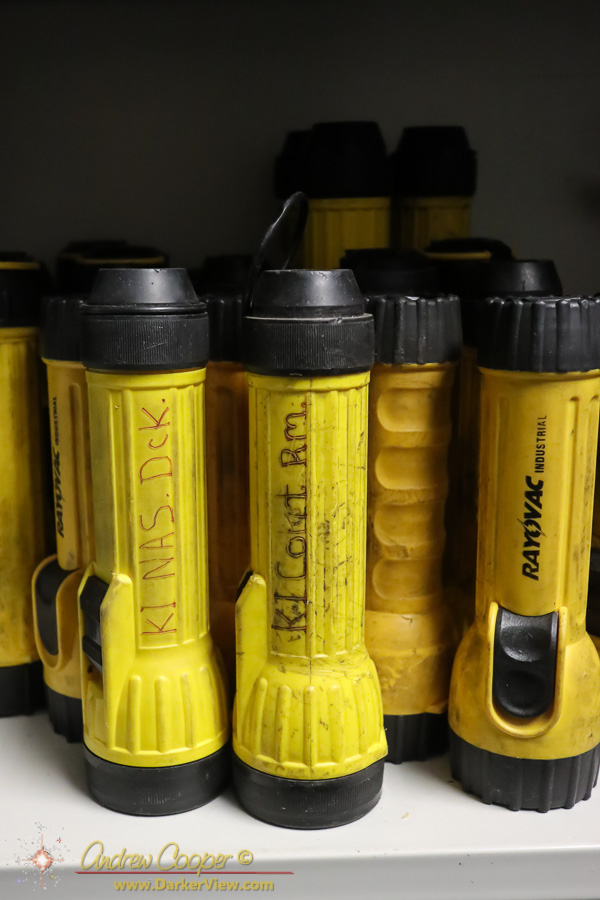 A collection of well used spare flashlights sitting on a shelf