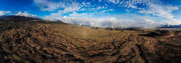 A panorama of the south flank of Mauna Kea showing old lava flows and puʻu