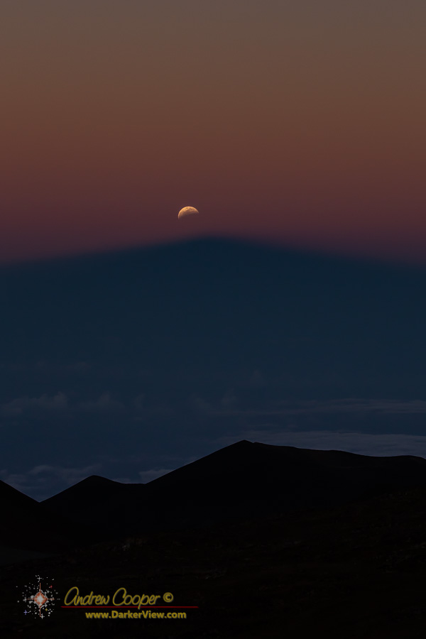 Partially eclipsed Moon rising above the shadow of Mauna Kea