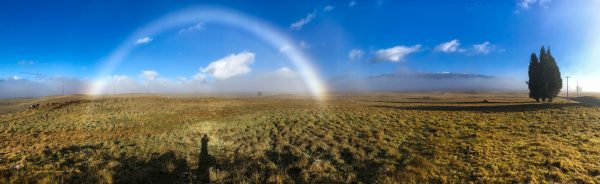 A morning fogbow along the access road leading to a snowy Mauna Kea