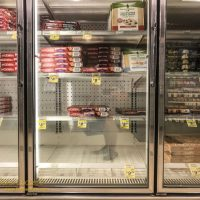 The frozen pizza case with empty shelves and a minimal selection