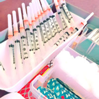 Syringes loaded with SARS-CoV-1 vaccine await use at a vaccination clinic